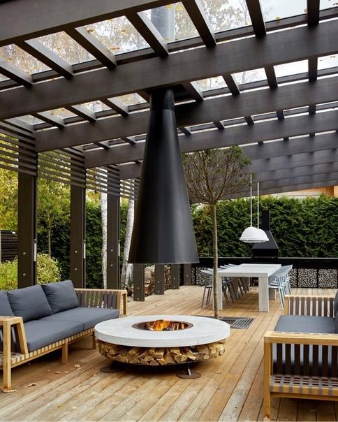 Стильная терраса с очагом и прозрачной крышей с дымоходом.